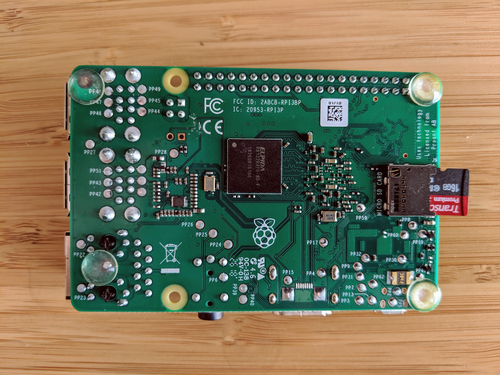 The bottom of a Raspberry Pi. A SD card is sticking out of it.