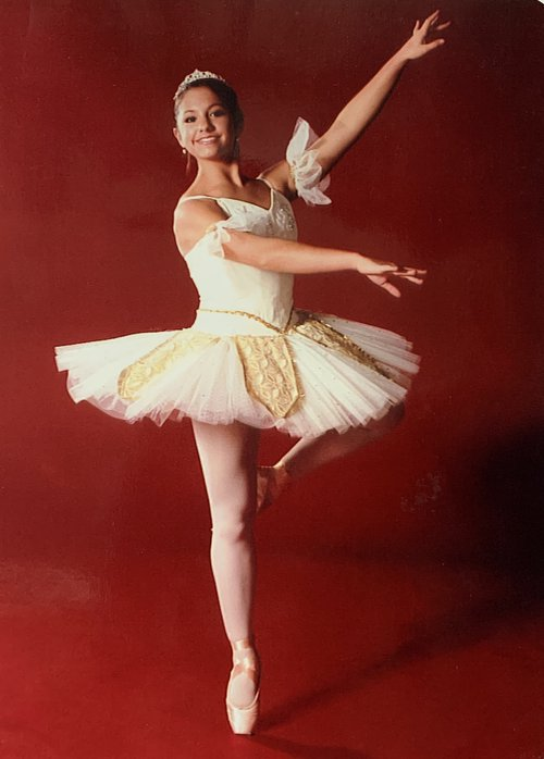 Photo of Liz Moy in a ballet position wearing a tutu against a red background