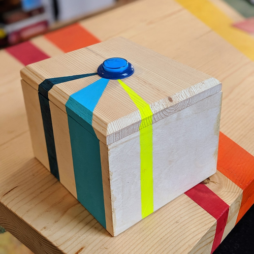 A wooden box with a blue button on the top sits on a table. The box has turquoise, teal, and neon yellow stripes.