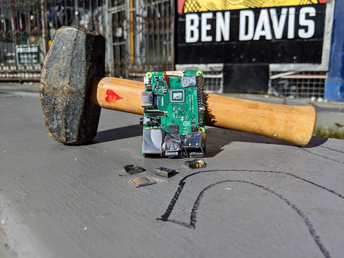 A smashed up Raspberry Pi sits propped against a mallet, on top of a concrete barrier. The mallet has a small heart drawn on it.
