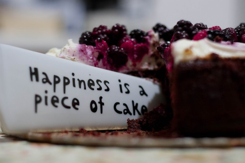 happiness is a piece of cake written on a knife cutting cake