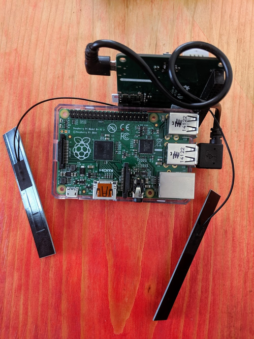 A Raspberry Pi sits on a table. A LTE Cat 1 Pi HAT is attached via the USB-A to micro USD ports. The hat sits next to the pi, but not on top of it, and the HAT has antennas attached.