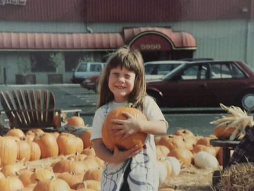 young august holding pumpkin